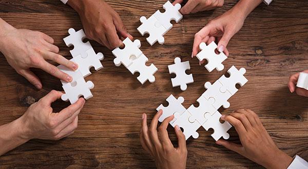 Mains qui assemblent un puzzle